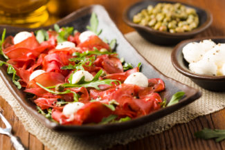 Beef carpaccio served with balls of mozzarella cheese, arugula and capers. Front view. Close-up.