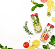 Infused water in bottles with various ingredients such as culinary aromatic herbs and fruits, healthy lifestyle concept, overhead view, blank space for a text