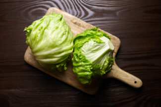 Iceberg,Lettuce,On,Cutting,Board,On,Wooden,Table,Background,,Top