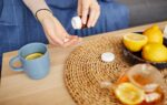 Close-up of woman taking vitamins and drinking tea with lemon at home