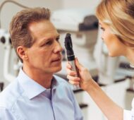 Young beautiful female ophthalmologist examining handsome middle aged man with modern equipment,close-up